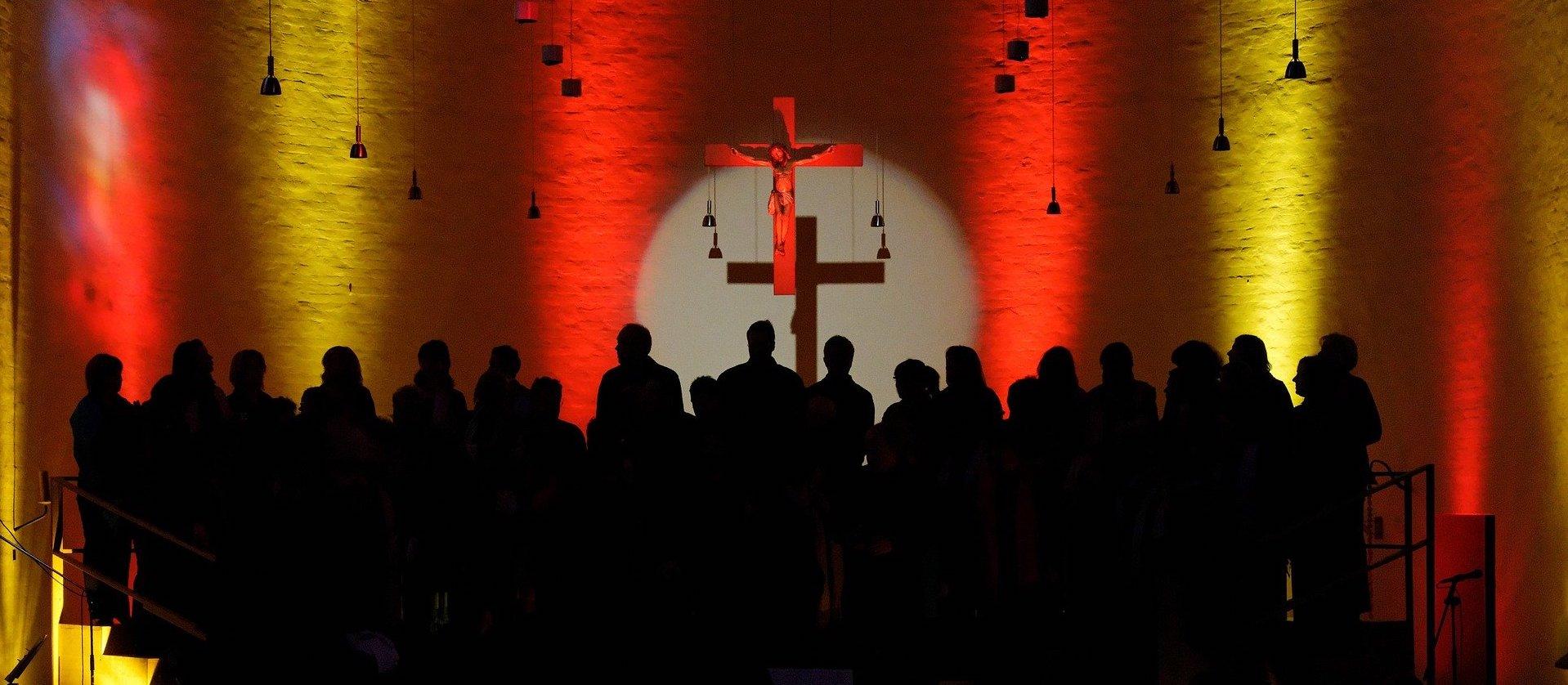 Silhouette eines Chors vor einem Kreuz