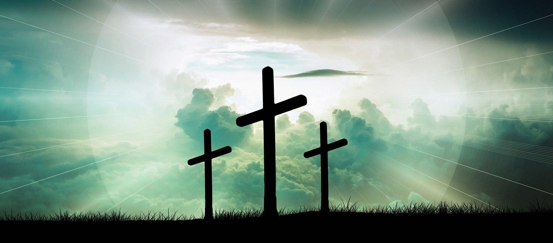 Silhouette von drei Kreuzen vor einem Leuchten im Hintergrund